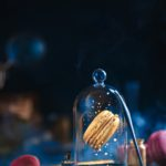 Precious golden macaron cookie under a glass dome. Pastry art, conceptual food photography
